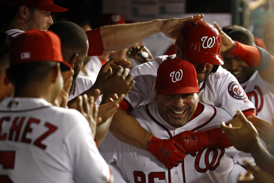 Washington Nationals batting practice pitcher Ali Modami, bottom right, carries Brian Dozier through the dugout after Dozier hit a solo home run during a game in September. (AP)