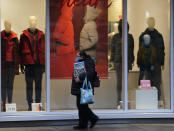 A pedestrian wears a mask while passing by a window display in a clothing store late Monday, Dec. 28, 2020, in downtown Denver. (AP Photo/David Zalubowski)