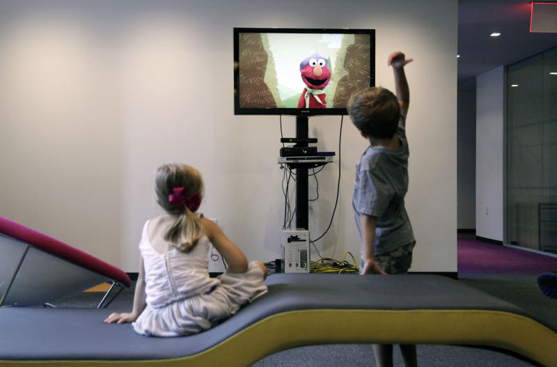 """In this Sept. 5, 2012, photo, from left, Zoe Shyba, 3, left, and Aidan Lain, 7, play """"Kinect Sesame Street TV"""" at the Sesame Street Workshop in New York. """"Kinect Sesame Street TV"""", launching Tuesday, Sept. 18, 2012, uses Kinect, a motion and voice-sensing controller created by Microsoft, to give Elmo, Big Bird and the rest of the Sesame Street crew a chance to have a real two-way conversation with their pint-sized audience. The effort represents the next step in the evolution of television, adding an interactive element to what's still largely a passive, lean-back experience. (AP Photo/Mark Lennihan)"""