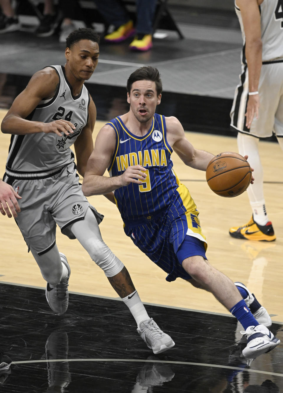Indiana Pacers' T.J. McConnell, right, drives around San Antonio Spurs' Devin Vassell during the second half of an NBA basketball game Saturday, April 3, 2021, in San Antonio. (AP Photo/Darren Abate)