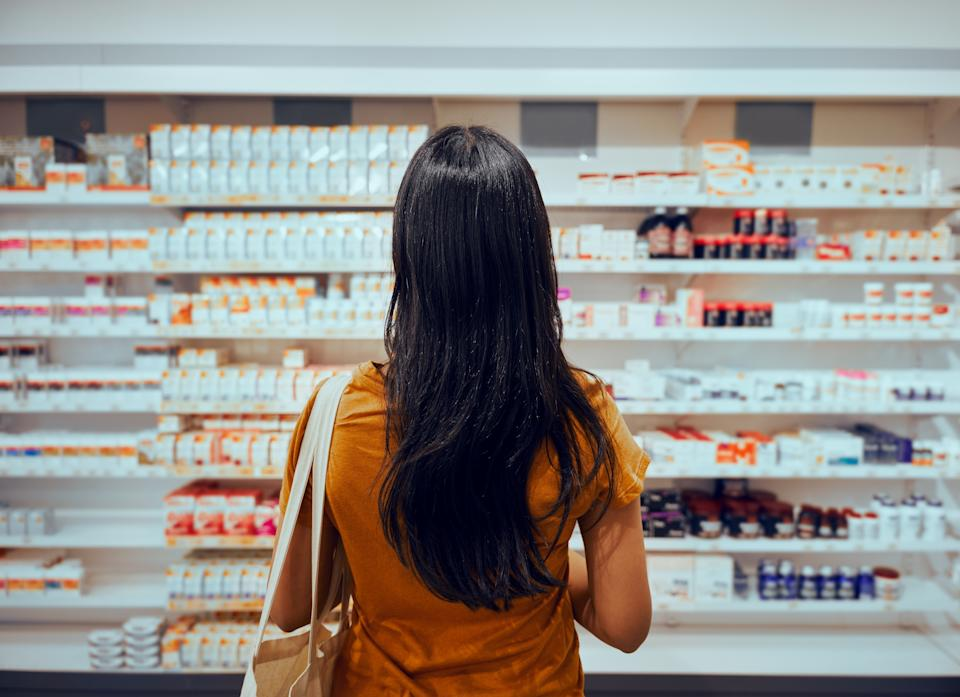 Young woman standing against shelf in pharmacy searching for medicine