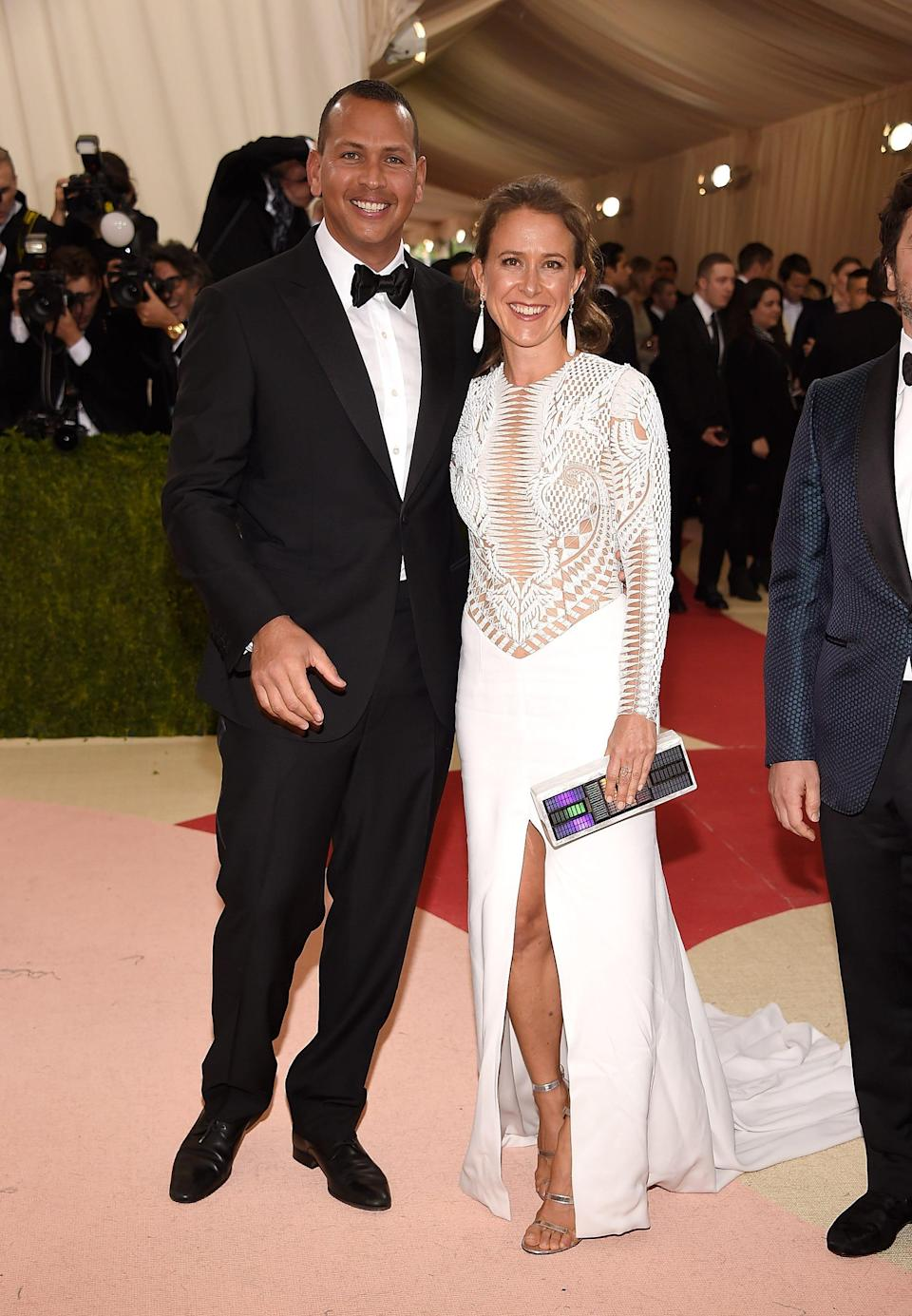 Alex Rodriguez stands in a suit and Anne Wojcicki stands in a white dress on a red carpet.