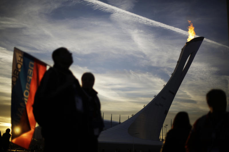 The Olympic flame burns as a spectator holding a Russian flag stands on the Olympic Plaza at the 2014 Winter Olympics, Thursday, Feb. 13, 2014, in Sochi, Russia. (AP Photo/David Goldman)