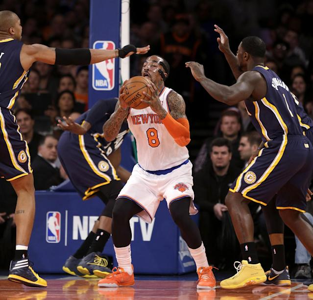 New York Knicks' J.R. Smith, center, looks to pass through Indiana Pacers defense during the first half of an NBA basketball game at Madison Square Garden on Wednesday, March 19, 2014, in New York. (AP Photo/Seth Wenig)