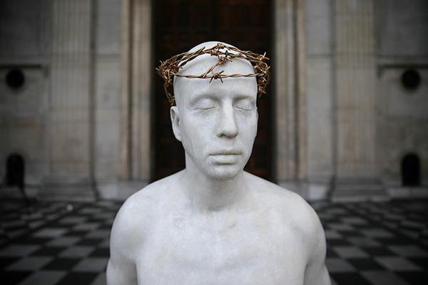 A statue of Jesus Christ, created by British artist Mark Wallinger and entitled 'Ecce Homo' is pictured on the steps of St. Paul's Cathedral in London on April 11, 2017, following its installation. The sculpture, created by the artist to appear on the fourth plinth in Trafalgar Square in 1999, has been placed outside the Cathedral in collaboration with Amnesty International and the Cathedral, to highlight the plight of all those currently in prison, suffering torture or facing execution because of their political, religious or other conscientiously-held beliefs, is set to remain in place until May 22.