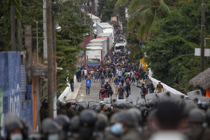 Honduran migrants, top, stand next to cargo trucks as they confront Guatemalan soldiers and police manning a roadblock the prevents them from advancing toward the US, on the highway in Vado Hondo, Guatemala, Monday, Jan. 18, 2021. The roadblock was strategically placed at a chokepoint on the two-lane highway flanked by a tall mountainside and a wall leaving the migrants with few options. (AP Photo/Sandra Sebastian)