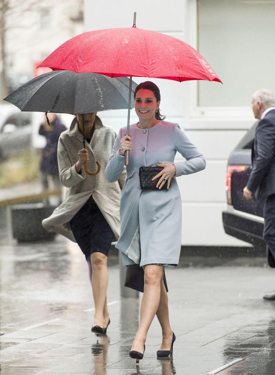 """<p>The Duchess stepped out on a rainy day in London in a pale blue cashmere blend coat <a href=""""https://www.seraphine.com/en-us/natasha-cashmere-blend-coat.html?"""" rel=""""nofollow noopener"""" target=""""_blank"""" data-ylk=""""slk:by Seraphine, which is still on sale for $299."""" class=""""link rapid-noclick-resp"""">by Seraphine, which is still on sale for $299.</a> She accessorized with a black clutch and black heels.</p>"""