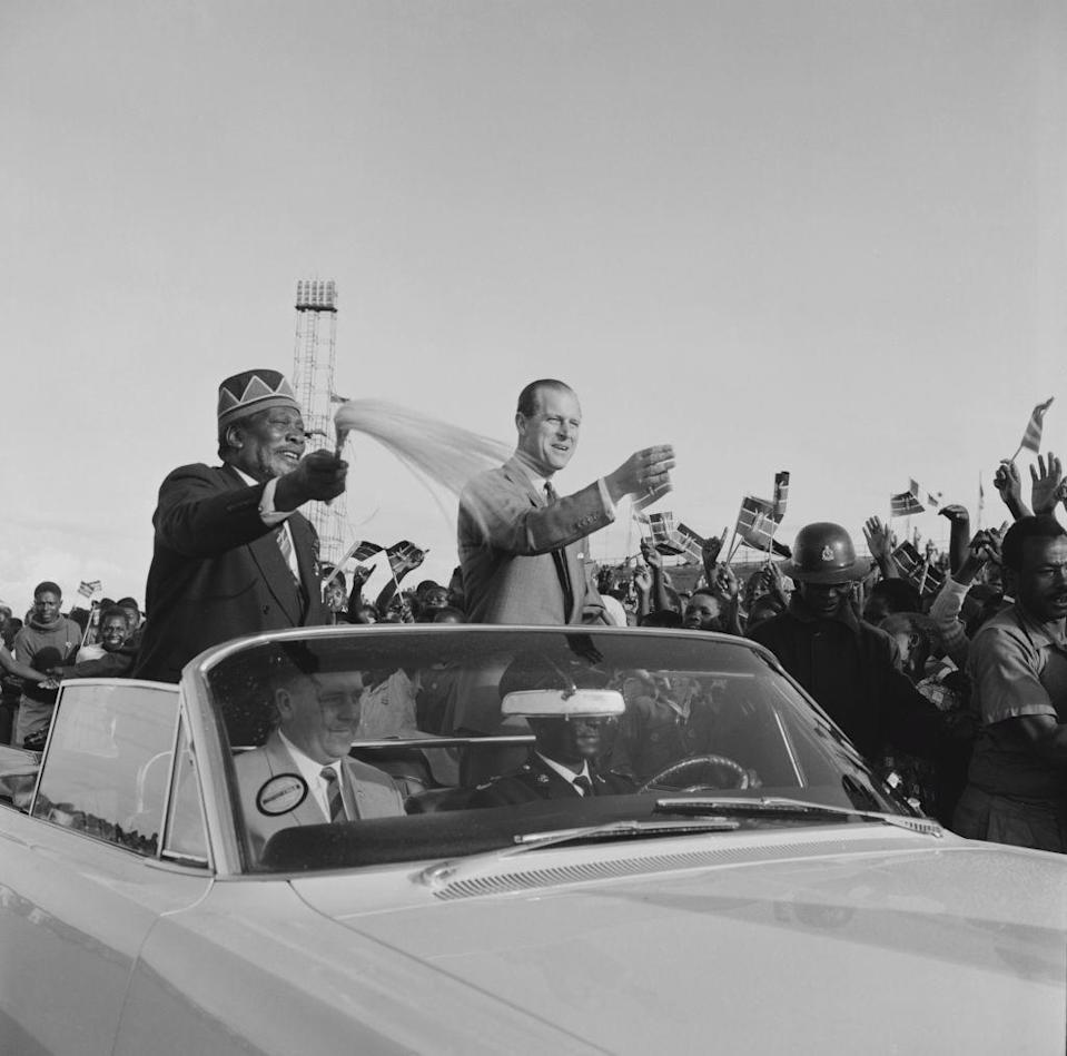 <p>Prince Philip stands in the rear seat of a car with the Prime Minister of Kenya, Jomo Kenyatta, as they wave to supporters and citizens during Independence celebrations in Kenya on 18 December, 1963.</p>