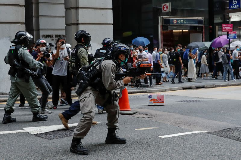 A riot police officer fires his weapon during a protest in Central, as a second reading of a controversial national anthem law takes place in Hong Kong