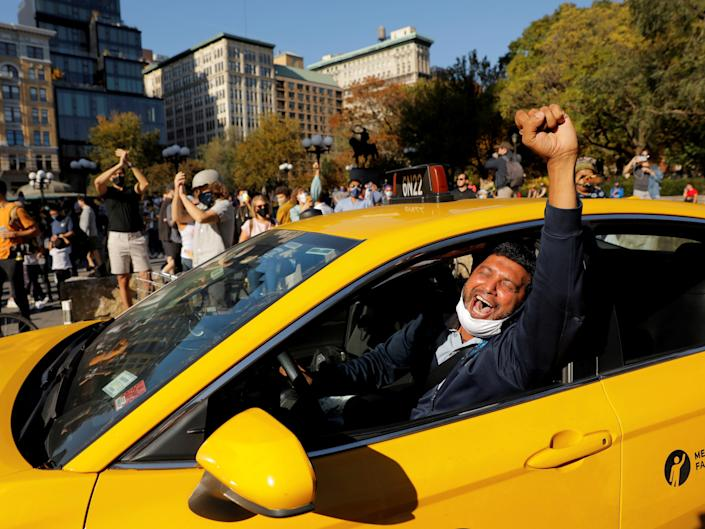 A cab driver raises his fist as people celebrate media announcements that Democratic U.S. presidential nominee Joe Biden has won the 2020 U.S. presidential election on Union Square in the Manhattan borough of New York City, U.S. November 7, 2020. REUTERS/Andrew Kelly