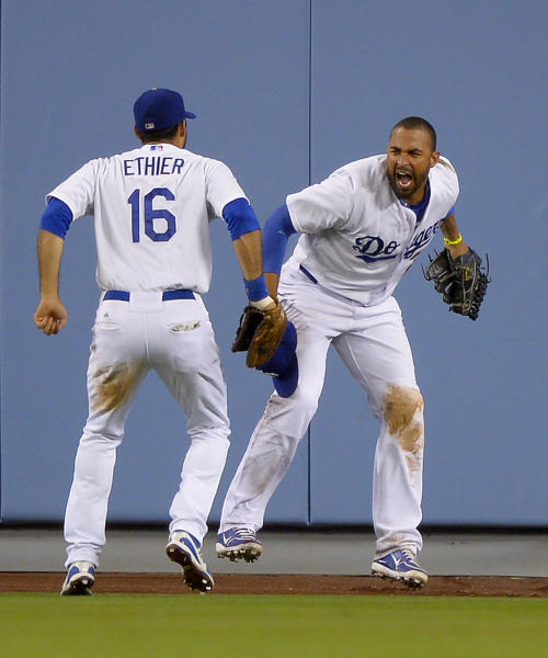 Los Angeles Dodgers center fielder Matt Kemp, right, celebrates with right fielder Andre Ethierafter making a catch on a ball hit by San Francisco Giants' Marco Scutaro to end their baseball game, Tuesday, June 25, 2013, in Los Angeles. The Dodgers beat the Giants 6-5. (AP Photo/Mark J. Terrill)