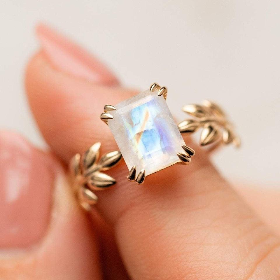 """<p>This <a href=""""https://www.popsugar.com/buy/Moon-Goddess-Ring-531775?p_name=Moon%20Goddess%20Ring&retailer=localeclectic.com&pid=531775&price=608&evar1=fab%3Aus&evar9=7954958&evar98=https%3A%2F%2Fwww.popsugar.com%2Fphoto-gallery%2F7954958%2Fimage%2F47032833%2FMoon-Goddess-Ring&list1=shopping%2Cwedding%2Cjewelry%2Crings%2Cengagement%20rings%2Cfashion%20shopping&prop13=api&pdata=1"""" rel=""""nofollow noopener"""" class=""""link rapid-noclick-resp"""" target=""""_blank"""" data-ylk=""""slk:Moon Goddess Ring"""">Moon Goddess Ring</a> ($608) features a large rectangle stone surrounded by a 14k solid gold band of laurel leaves.</p>"""