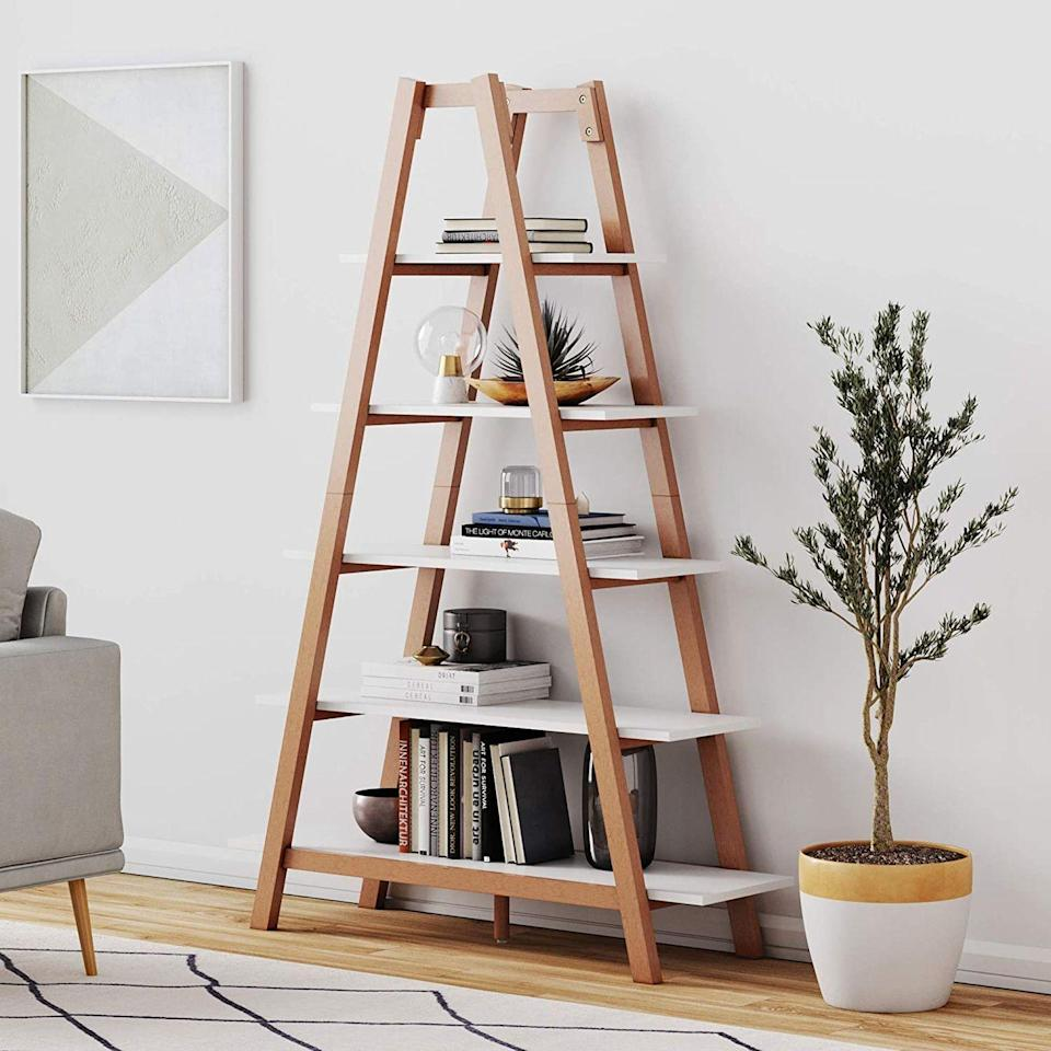 """<p>An a-frame shelving unit like the <a href=""""https://www.amazon.com/Nathan-James-62201-Bookcase-Decorative/dp/B07YSL7ZCV?ref_=ast_sto_dp&th=1&psc=1&tag=syn-yahoo-20&ascsubtag=%5Bartid%7C10067.g.37858770%5Bsrc%7Cyahoo-us"""" rel=""""nofollow noopener"""" target=""""_blank"""" data-ylk=""""slk:Carlie Bookshelf"""" class=""""link rapid-noclick-resp"""">Carlie Bookshelf</a> from Nathan James is a practical and stylish way to store your favorite reads and trinkets alike. Best of all, Nathan James products come highly rated by thousands of Amazon customers. <em>Every</em> product has at least four stars. </p><p><a class=""""link rapid-noclick-resp"""" href=""""https://www.amazon.com/stores/page/B267ACAD-8A5C-4A01-B397-CDB97D05D28D?ingress=2&visitId=cebd79e8-9b69-4aab-91a6-cf8521886e60&ref_=ast_bln&tag=syn-yahoo-20&ascsubtag=%5Bartid%7C10067.g.37858770%5Bsrc%7Cyahoo-us"""" rel=""""nofollow noopener"""" target=""""_blank"""" data-ylk=""""slk:Shop Nathan James on Amazon"""">Shop Nathan James on Amazon</a></p>"""