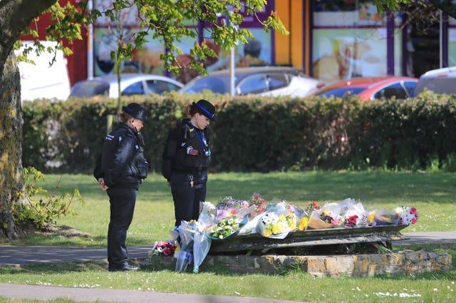 Police community support officers look at flowers left in memory of PCSO Julia James in Aylesham, Kent