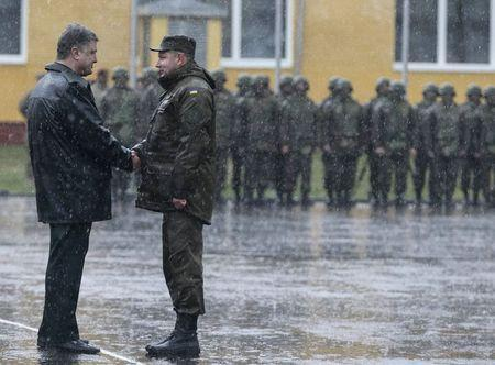 """Ukraine's President Petro Poroshenko (L) shakes hands with a serviceman of Ukrainian National Guard during an opening ceremony of joint military exercise """"Fearless Guardian 2015"""" at the International Peacekeeping Security Center near the village of Starychy western Ukraine, April 20, 2015. REUTERS/Gleb Garanich"""