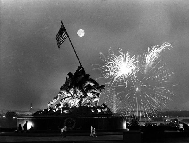 <p>This view, from the Virginia side of the Potomac River, shows the moon above the Iwo Jima Statue as fireworks burst over Washington, D.C., on July 4, 1966. The Washington Monument, obelisk, and the Lincoln Memorial can be seen in the background. (Photo: Charles Tasnadi/AP) </p>