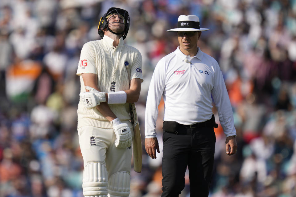 England's Craig Overton holds his arm as he leaves the pitch after he is bowled by India's Umesh Yadav on day five of the fourth Test match at The Oval cricket ground in London, Monday, Sept. 6, 2021. (AP Photo/Kirsty Wigglesworth)