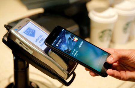 Man uses iPhone 7 smartphone to demonstrate mobile payment service Apple Pay at cafe in Moscow