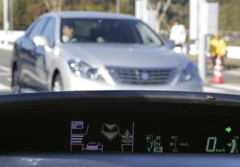 A human sign and an arrow pop up on a dashboard display to notify the driver of a pedestrian's presence and an approaching car at the coming intersection during a demonstration of Toyota Motor Corp.'s Intelligent Transport System at its Higashi-Fuji Technical Center in Susono, southwest of Tokyo, Monday, Nov. 12, 2012. Toyota is testing out safety systems using cars that communicate with each other and with the roads they are on in a just-completed facility in Japan, the size of three baseball stadiums. (AP Photo/Koji Sasahara)