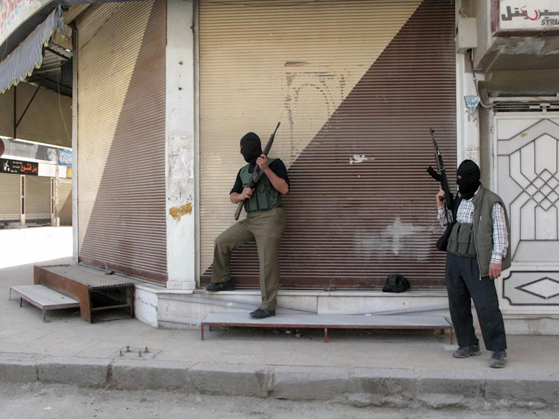 In this Friday, April 6, 2012 photo, Free Syrian Army fighters stand guard during fighting with Syrian troops in a suburb of Damascus, Syria. Syrian government shelling and offensives against rebel-held towns killed dozens of people across the country on Saturday, activists said, as the U.S. posted online satellite images of troop deployments that cast further doubt on whether the regime intends to comply with an internationally sponsored peace plan. (AP Photo)
