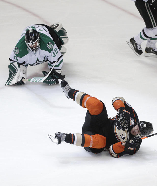 Anaheim Ducks' Corey Perry, bottom, stumbles after he scored against Dallas Stars goalie Tim Thomas, top, during the third period of Game 5 of the first-round NHL hockey Stanley Cup playoff series on Friday, April 25, 2014, in Anaheim, Calif. (AP Photo/Jae C. Hong)