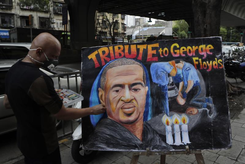 An artist from Gurukul art school works on a poster paying tribute to George Floyd, an African American man who died on May 25 as a Minneapolis police officer pressed his knee into his neck, ignoring his cries and bystander shouts until he eventually stopped moving, in Mumbai, India, Thursday, June 11, 2020. (AP Photo/Rajanish Kakade)