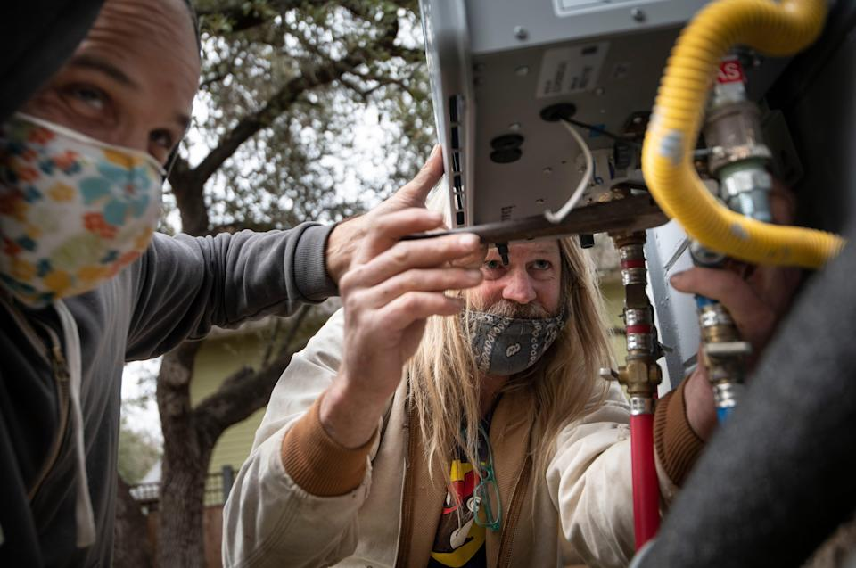 Michael Kunitzky and Coleman Kelly of the Austin Guerrilla Plumber Corps work to replace a water heater Thursday, Feb. 25, 2021 in Austin, Texas. The corps of five friends, is working to repair underprivileged residents' plumbing problems caused by the winter storm.