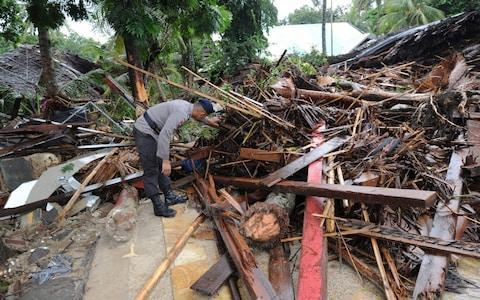 <span>An Indonesia policeman searches for victims amongst the debris at the Mutiara Carita Cottages in Carita in Banten province </span>