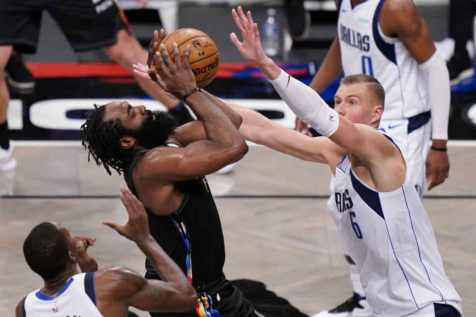 Brooklyn Nets guard James Harden, center left, shoots against Dallas Mavericks center Kristaps Porzingis (6) during the second half of an NBA basketball game Saturday, Feb. 27, 2021, in New York. (AP Photo/John Minchillo)
