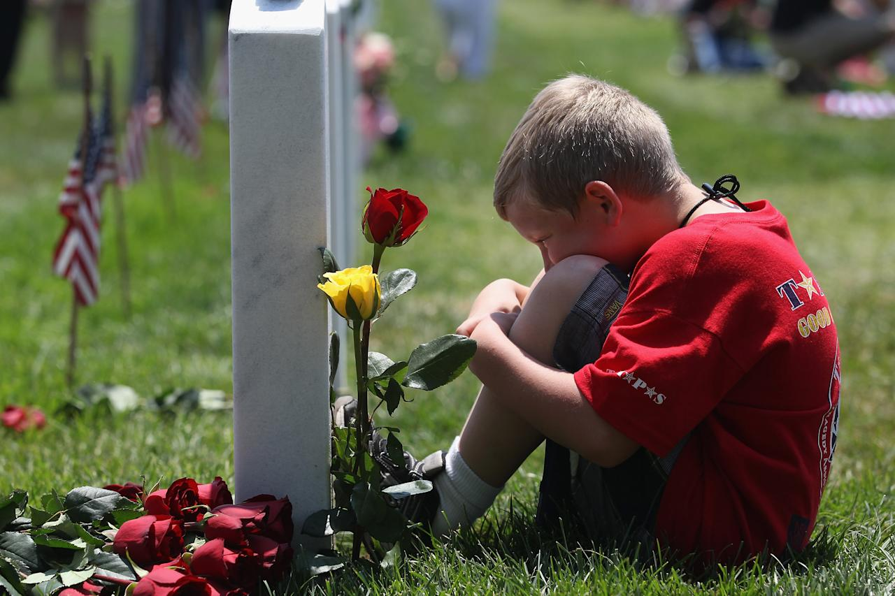 "Wyatt McCain, 8, from North Pole, Alaska, looks upon his father's grave at the National Cemetery on Memorial Day on May 28, 2012 in Arlington, Virginia. His dad, Army SFC Johnathan McCain, was killed by a roadside bomb in Afghanistan in November 2011. Wyatt came with his mother and three sisters to take part in a TAPS ""Good Grief Camp"". Five hundred military children and teens, many of whom had a parent that was killed in the Afghan and Iraq wars, attended the annual four-day ""Good Grief Camp"" in Arlington, VA and Washington, DC, which is run by TAPS (Tragedy Assistance Program for Survivors). The camp helped them learn coping skills and build relationships so they know they are not alone in the grief of their loved one. They met others of their own age group, learned together and shared their feelings, both through group activities and one-on-one mentors, who are all active duty or former military servicemembers. Some 1,200 adults, most of whom are grieving parents and spouses, also attend the National Military Survival Seminar held concurrently with the children's camp. The TAPS slogan is ""Remember the Love. Celebrate the Life. Share the Journey.""  (Photo by John Moore/Getty Images)"