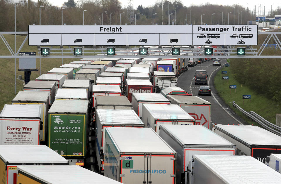 Heavy good lorries queue to enter the Eurotunnel site in Folkestone, southern England, as French customs officers continue their work-to-rule industrial action, Tuesday March 19, 2019.  French customs workers are protesting over pay and to show the effect of Britain's Brexit from Europe will have on cross-Channel traffic. (Gareth Fuller/PA via AP)