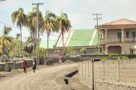 Men walk down a street after a series of eruptions from La Soufriere volcano