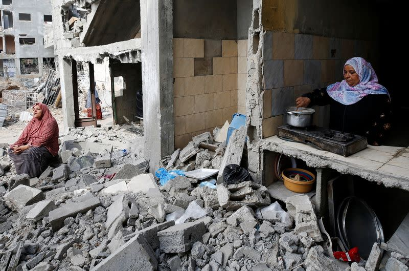 A Palestinian woman cooks as another sits amid the rubble of their houses destroyed by Israeli air strikes