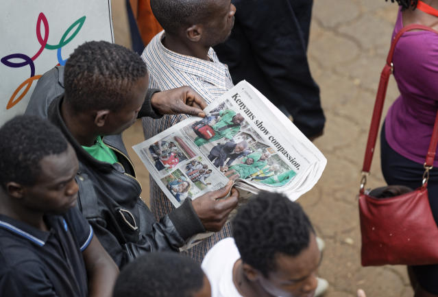 Kenyans read newspapers at the scene of the attack Wednesday, Jan. 16, 2019 in Nairobi, Kenya. Extremists stormed a luxury hotel in Kenya's capital on Tuesday, setting off thunderous explosions and gunning down people at cafe tables in an attack claimed by Africa's deadliest Islamic militant group. (AP Photo/Ben Curtis)