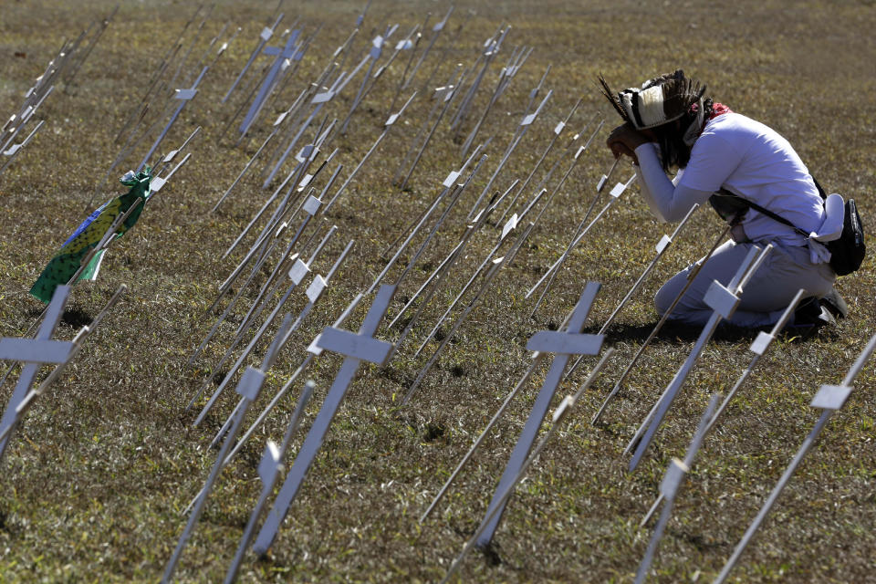 A demonstrator kneels before rows of crosses representing the thousands of deaths due to the new coronavirus, during a protest demanding President Jair Bolsonaro be impeached, in front of the National Congress in Brasilia, Brazil, Tuesday, July 14, 2020. As Brazil careens toward a full-blown public health emergency and economic meltdown, opponents have filed a request for Bolsonaro's impeachment based on his mishandling of the new coronavirus pandemic. (AP Photo/Eraldo Peres)