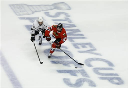 Chicago Blackhawks left wing Brandon Saad (20) brings the puck up the ice against Los Angeles Kings left wing Kyle Clifford (13) during the first period in Game 1 of the NHL hockey Stanley Cup Western Conference finals Saturday, June 1, 2013, in Chicago. (AP Photo/Charles Rex Arbogast)