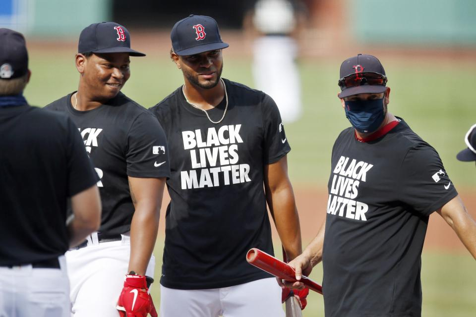 Boston Red Sox's Rafael Devers, left, and Xander Bogaerts, center, wear Black Lives Matter jerseys during warmups before an opening day baseball game against the Baltimore Orioles at Fenway Park, Friday, July 24, 2020, in Boston. (AP Photo/Michael Dwyer)