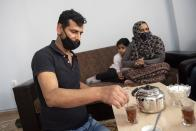 Abdul Salam Al Khawien, 37, serves tea at his apartment in the northern city of Thessaloniki, Greece, Saturday, May 1, 2021. Sundered in the deadly chaos of an air raid, a Syrian family of seven has been reunited, against the odds, three years later at a refugee shelter in Greece's second city of Thessaloniki. (AP Photo/Giannis Papanikos)