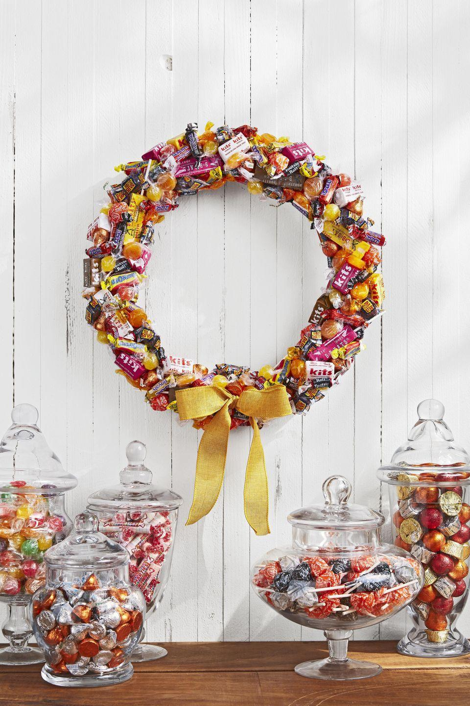 <p>Hang on the door for decoration or let trick-or-treaters help themselves to a sweet treat.<br></p><p>Gather an assortmentof old-fashioned candies in autumnal shades such as yellow, orange, and magenta. Wrap a 14-inch foam wreath form in white ribbon. Attach candy with hot-glue, layering and overlapping as you go. Finish with a yellow burlap bow. </p>