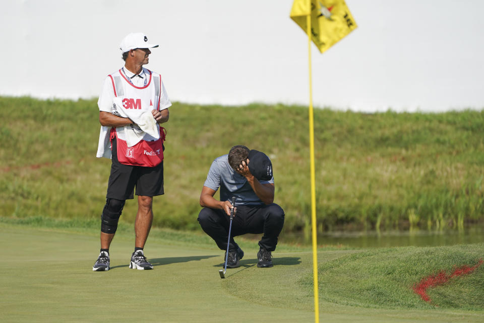 Cameron Champ, right, takes a moment with his caddie Chad Reynolds, before making his final shot and winning the 3M Open golf tournament in Blaine, Minn., Sunday, July 25, 2021. (AP Photo/Craig Lassig)