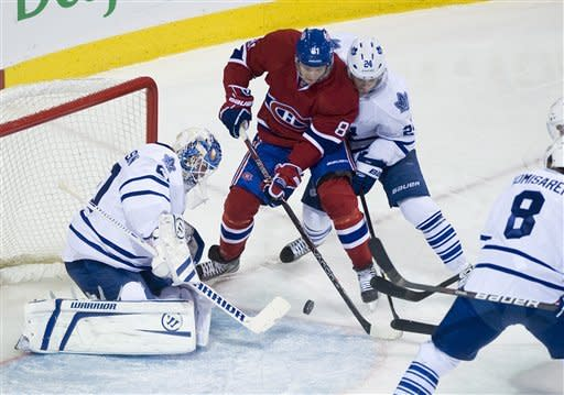 Montreal Canadines' Lars Eller (81) shoots on Toronto Maple Leafs goaltender Jonas Gustavsson, left, as Leafs' John-Michael Liles (24) defends during first period NHL hockey game action in Montreal, on Saturday, March 3, 2012. (AP Photo/The Canadian Press, Graham Hughes)