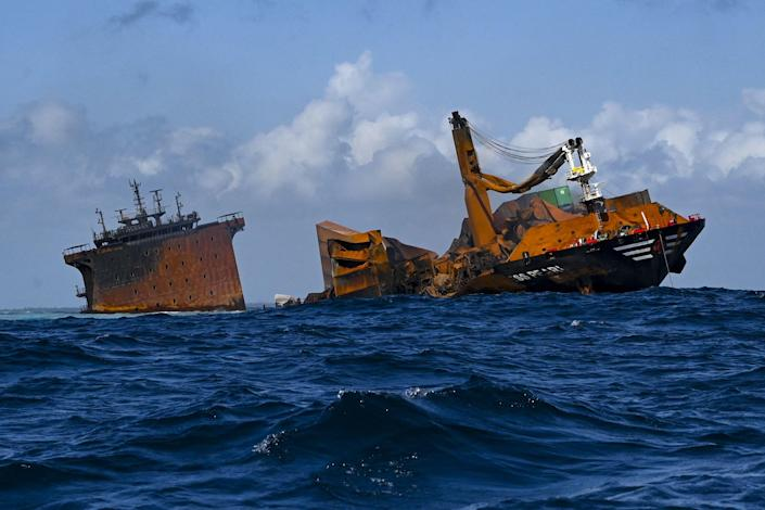 The fire stricken Singapore-registered container ship MV X-Press Pearl (L) is seen sinking while being towed away from the coast of Colombo, June 2, 2021, following Sri Lankan President Gotabaya Rajapaksa's order to move the ship to deeper water to prevent a bigger environmental disaster. / Credit: ISHARA S. KODIKARA/AFP/Getty
