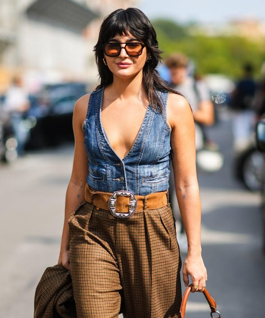 MILAN, ITALY – SEPTEMBER 23: Maria Bernad wears sunglasses, silver and gold large earrings, a blue faded denim V-neck buttoned sleeveless jacket, a brown shiny leather with burgundy and dark green print pattern in coated canvas shoulder bag from Etro, a brown with red and black checkered print pattern blazer jacket, matching brown with red and black checkered print pattern large suit pants, a brown suede belt with a silver large western buckle, black leather pointed block heels ankle boots, outside the Etro fashion show during the Milan Fashion Week – Spring / Summer 2022 on September 23, 2021 in Milan, Italy. (Photo by Edward Berthelot/Getty Images)