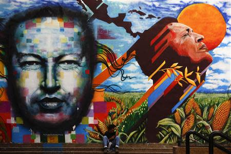 A man sits next to a mural depecting the late Venezuelan President Hugo Chavez in downtown Caracas