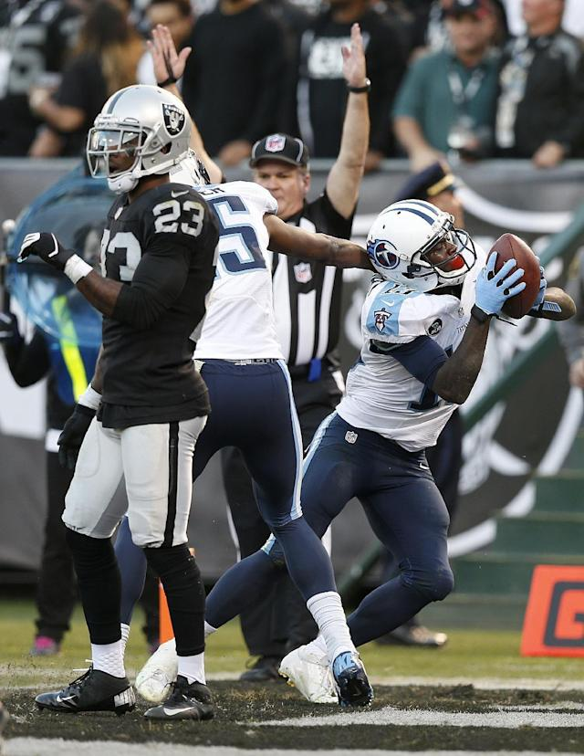 Tennessee Titans wide receiver Kendall Wright, right, celebrates after scoring on a 10-yard touchdown pass behind Oakland Raiders cornerback Tracy Porter (23) during the fourth quarter of an NFL football game in Oakland, Calif., Sunday, Nov. 24, 2013. The Titans won 23-19. (AP Photo/Beck Diefenbach)