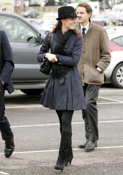 <p>Attending day four of the Cheltenham Horse Racing Festival in a black fedora and navy trench coat. </p>