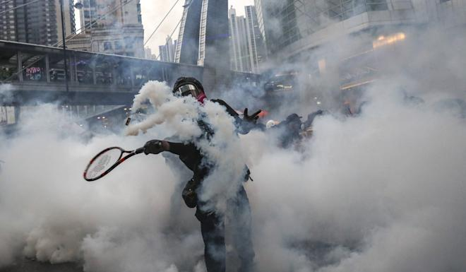 A protester uses a tennis racket to return a tear-gas canister fired by police in Tsuen Wan on August 25. Photo: Sam Tsang