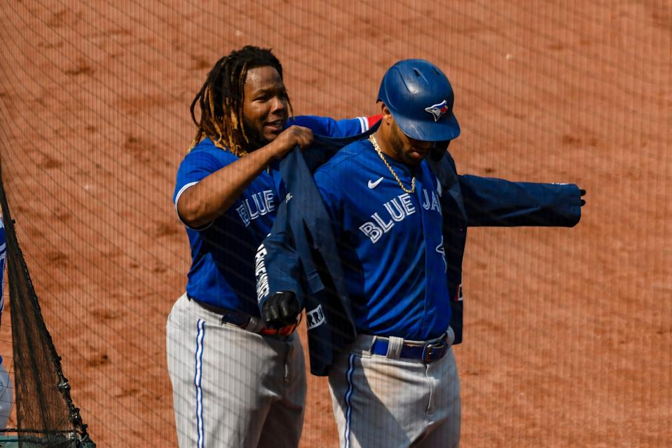 Vladimir Guerrero Jr. and Lourdes Gurriel Jr. celebrate with the team's home run jacket in Baltimore.