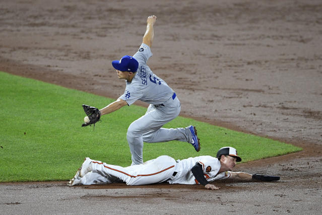 Baltimore Orioles' Austin Hays, bottom, slides toward second, advancing on a wild pitch as Los Angeles Dodgers shortstop Corey Seager (5) reaches for the ball during the third inning of a baseball game Wednesday, Sept. 11, 2019, in Baltimore. (AP Photo/Nick Wass)