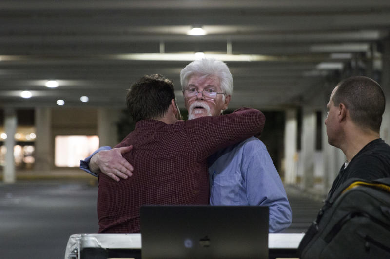 FILE - In this June 28, 2018, file photo, the Capital Gazette reporters Pat Furgurson, center, and Chase Cook hug at a makeshift office in a parking garage of a mall in Annapolis, Md., during coverage of the fatal shootings that happened in their paper's newsroom earlier in the day. Reporters who survived the worst attack on journalists in U.S. history say the trauma has not faded, but their connection with their readers is a source of comfort and inspiration. (Thalia Juarez/The Baltimore Sun via AP)